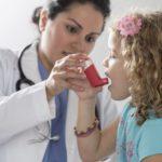 A physician helping a child with an inhaler