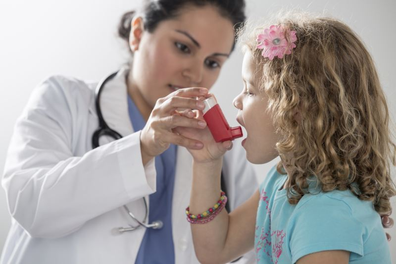 A physician helping a child with an inhaler