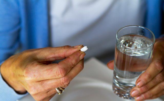 Beta blocker, woman taking white pill, medicine