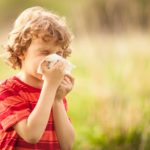 Child sneezing, blowing nose