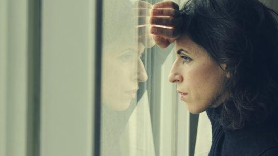depresssed woman looking out window
