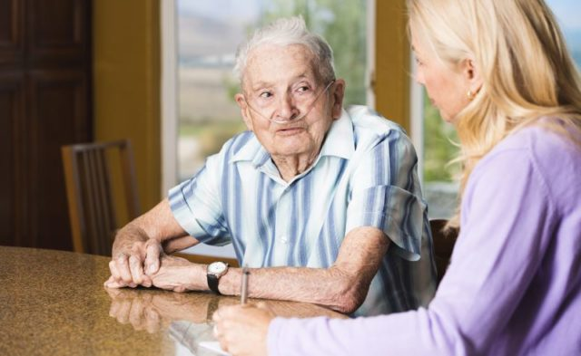 A nurse speaking with an elderly man in a home setting