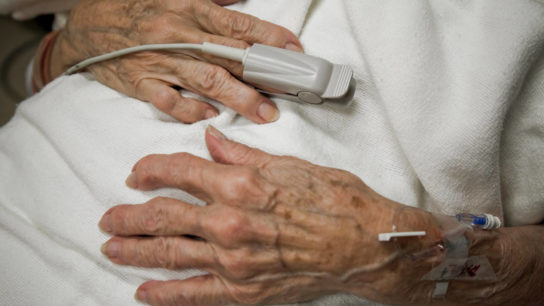 Elderly woman's hands in hospital room, IV drip, oxygen monitor