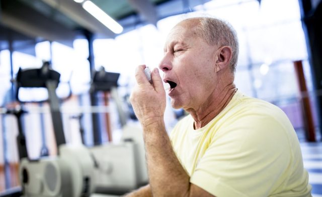 older man at the gym using an inhaler