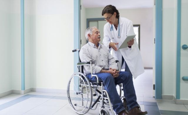 Hospital patient in wheelchair speaking with doctor