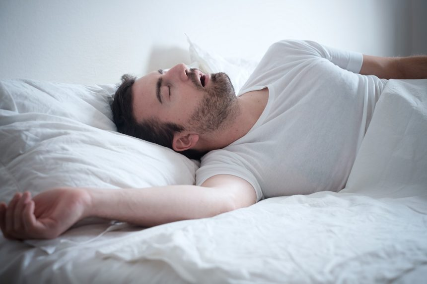 Man sleeping and snoring in bed