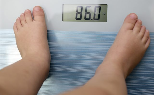 Child standing on scale, obesity, overweight