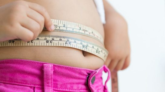An overweight child's stomach with a tape measure