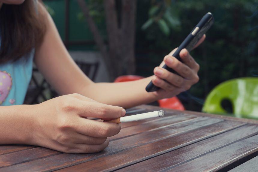 Woman smoking cigarette, holding cellphone