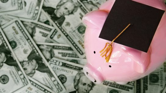 piggy bank with graduation cap on cash