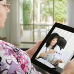 Woman connecting with doctor through tablet, telemedicine