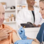 elderly man receiving influenza vaccine