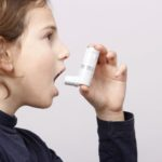 girl with asthma holding inhaler