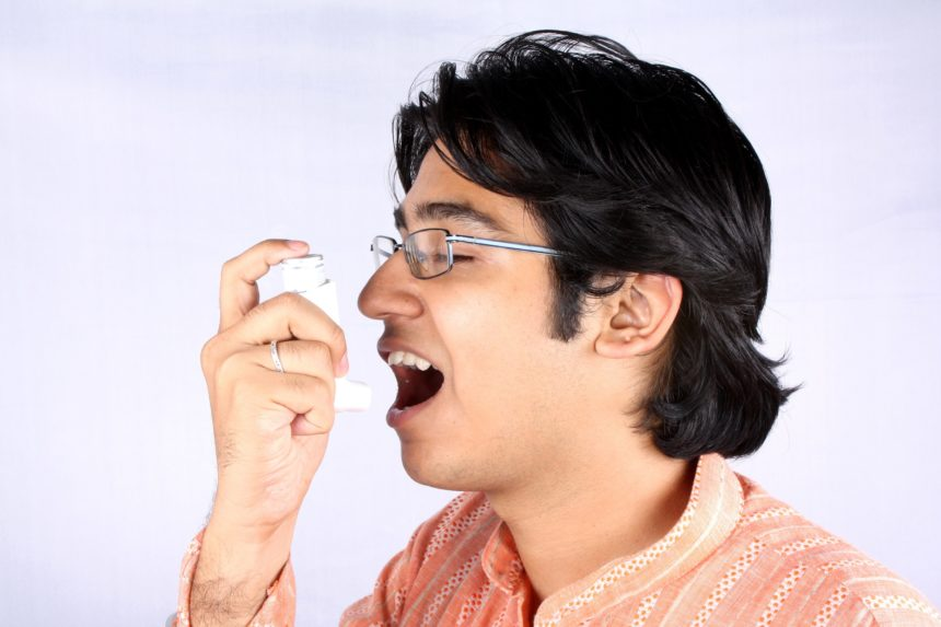 young Indian man with asthma inhaler