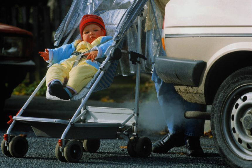 baby in stroller next to car