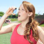 Woman using an inhaler after jogging