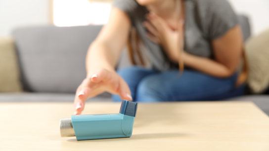 woman having an asthma attack and reaching for an inhaler