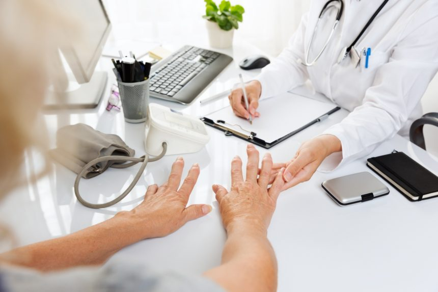 doctor looking at old lady hands