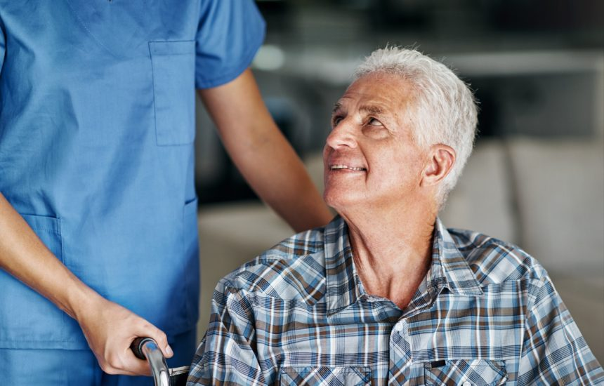 older patient in wheelchair pushed by nurse