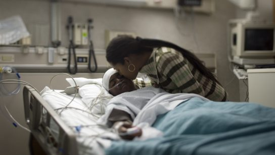 Black child in intensive care unit, hospital with parent